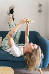 Laughing young woman lying on couch using cell phone - AFVF04486