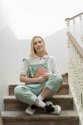 Portrait of smiling young woman sitting in staircase holding notebook - AFVF04510