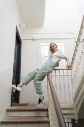 Carefree young woman sliding on railing in staircase - AFVF04513