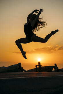 Silhouette of ballerina daning at sunset - MPPF00412