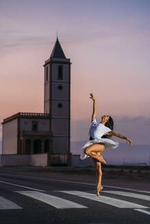 Ballerina dancing in front of a church in the evening - MPPF00415