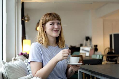 Deutschland; NRW; Ruhrgebiet; Essen; junge Frau im Café und lächelt - FLLF00362