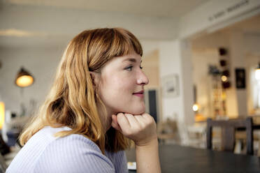 Portrait of strawberry blonde young woman with nose piercing in a cafe - FLLF00365