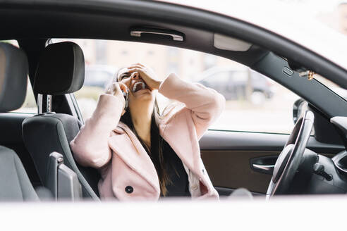 Laughing businesswoman using smartphone in the car - CJMF00207