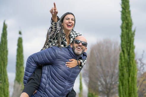 Businesswoman and attractive man smiling, man carrying woman on his back - CJMF00213
