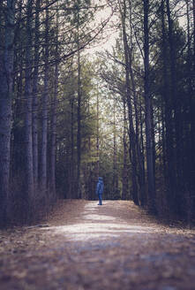 Full length of boy standing on dirt road amidst forest - CAVF70844