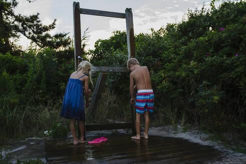 Rear view of siblings washing legs from tap water at Tobay Beach - CAVF70880