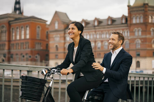 Smiling businesswoman and businessman traveling on bicycle in city - MASF15518