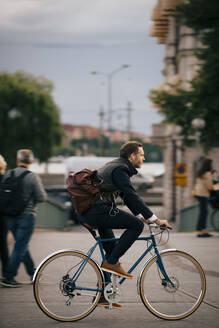 Side view of confident businessman riding bicycle on street in city - MASF15521