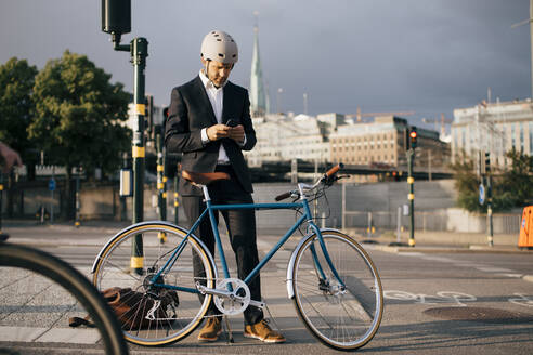 Businessman using mobile phone while standing by bicycle on street in city - MASF15539
