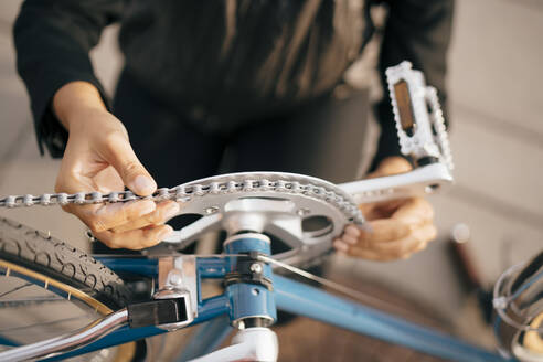 Midsection of businesswoman repairing bicycle in city - MASF15542