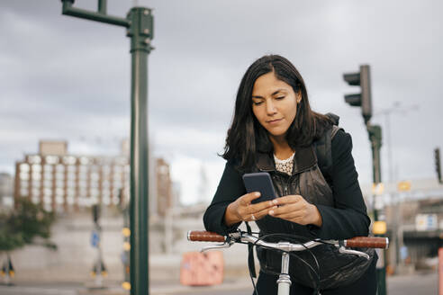 Businesswoman using mobile phone while leaning on bicycle handle in city - MASF15545