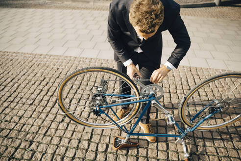 High angle view of businessman repairing bicycle chain on cobbled footpath in city - MASF15551