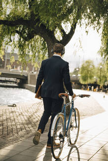 Rear view of businessman walking with bicycle on footpath in city - MASF15563