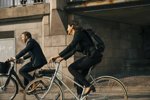 Side view of businessman and businesswoman riding bicycles on street in city - MASF15566