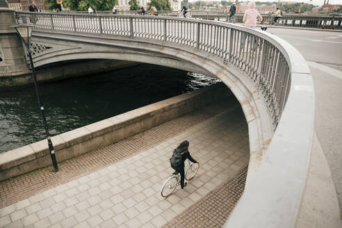 High angle view of businesswoman cycling on footpath by canal in city - MASF15569