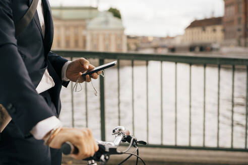 Midsection of businessman using mobile phone while walking with bicycle on bridge in city - MASF15581