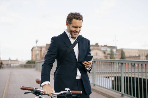 Smiling businessman using mobile phone while walking with bicycle on bridge in city - MASF15584