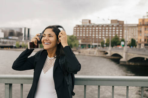 Smiling businesswoman wearing headphones while standing on bridge in city - MASF15587