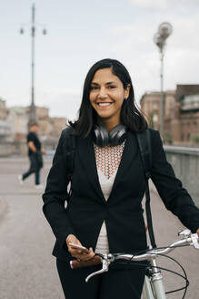 Portrait of smiling businesswoman with bicycle on bridge in city - MASF15590