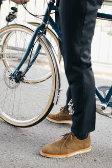 Low section of businessman with bicycle on street in city - MASF15593