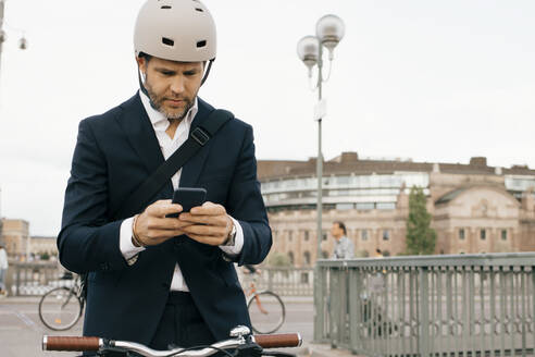 Businessman using mobile phone while standing with bicycle on bridge in city - MASF15599