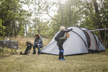 Siblings playing while man sitting with dog by tent at camping site - MASF15635