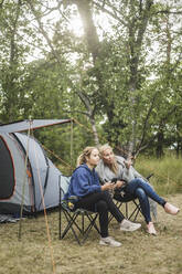 Full length of woman talking to daughter while sitting at campsite - MASF15638
