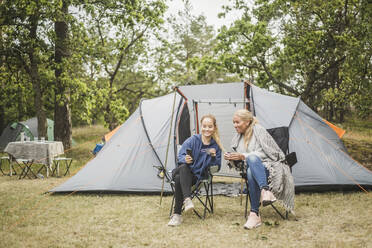 Daughter showing mobile phone to mother while having coffee outside tent - MASF15641