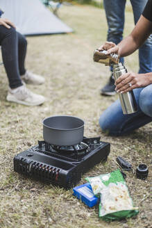 Cropped image of woman preparing coffee on camping stove - MASF15644