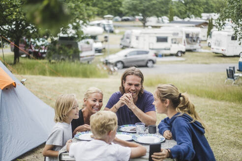 Happy family talking while having food together at table by tent - MASF15647