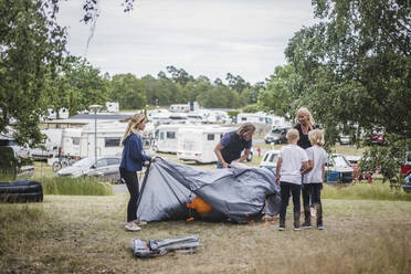 Children assisting parents in pitching tent at camping site - MASF15668