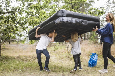 Full length of teenage girl having fun with siblings while carrying inflatable mattress together at camping site - MASF15671