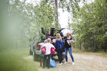 Parents with children unloading luggage from car at camping site during vacation - MASF15674
