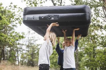 Siblings carrying inflatable mattress walking at camping site - MASF15677