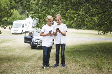 Girl showing mobile phone to brother while standing at camping site - MASF15680