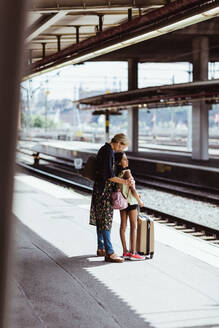 Full length of mother and daughter waiting at railroad station platform - MASF15803