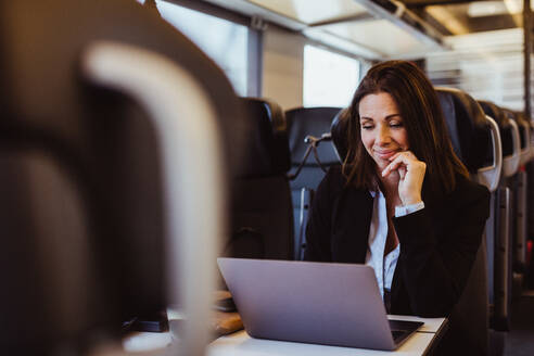 Smiling businesswoman using laptop while sitting in train - MASF15860
