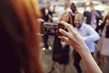 Cropped image of executive photographing coworkers on smart phone at terrace in office party - MASF15902