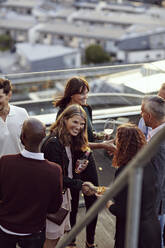 Happy professionals greeting at party on terrace after work - MASF15905