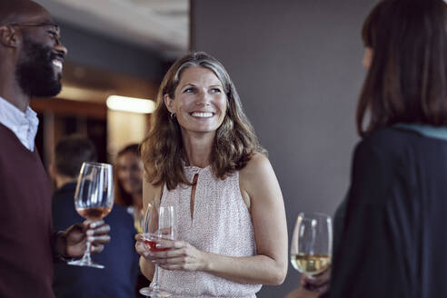 Smiling business people talking over drinks in office party - MASF15917