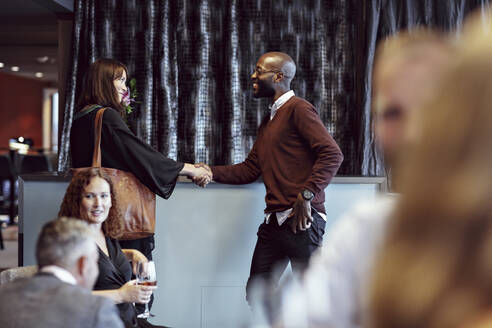 Business colleagues shaking hands while greeting during office party after work - MASF15926