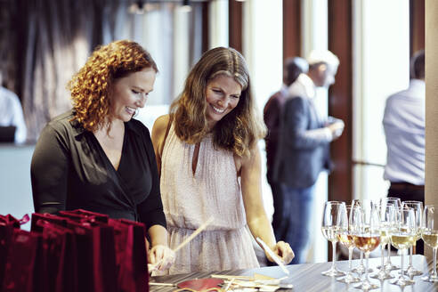Smiling businesswomen looking at props by wineglasses on table in office party - MASF15929