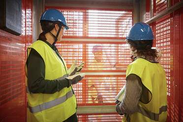 Female engineers discussing while standing in freight elevator at construction site - MASF15971