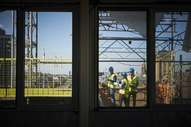 Male and female architects seen through window at construction site - MASF15977
