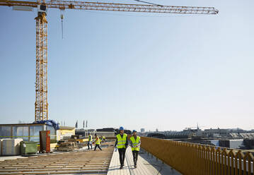 Female coworkers walking at construction site against clear sky - MASF15980