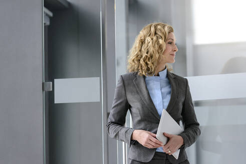 Confident businesswoman holding tablet in office - BMOF00090