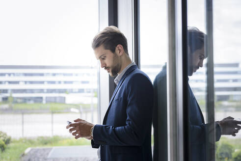 Young businessman using smartphone at the window - BMOF00102