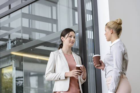 Two businesswomen having coffee break outside office building - BMOF00105