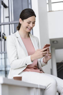 Happy young businesswoman using smartphone in office - BMOF00108